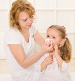 Woman blowing little girls nose Royalty Free Stock Photography