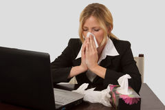 Woman blowing nose. Blond caucasian woman wearing business attire sitting in front of laptop computer with a box of tissues blowing her nose Royalty Free Stock Images