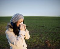 Woman blowing nose. A Woman in countryside blowing her nose Stock Photography
