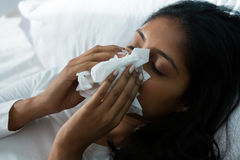 Woman blowing nose on bed. Woman blowing nose while relaxing on bed at home Stock Image