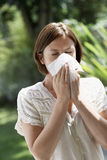Woman Blowing Nose In Park. Young woman blowing nose with tissue paper in park Stock Photography