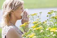 Woman blowing nose into tissue in front of flowers. Side view of woman blowing nose into tissue in front of flowers Royalty Free Stock Images