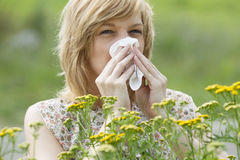 Woman blowing nose into tissue outdoors. Young woman blowing nose into tissue in front of flowers Royalty Free Stock Photography
