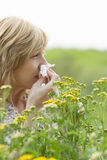 Woman blowing nose into tissue outdoors. Side view of woman blowing nose into tissue in front of flowers Stock Images