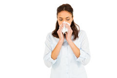 Woman blowing nose with tissue paper. Against white background Stock Photography