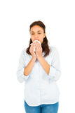 Woman blowing nose with tissue paper. Against white background Stock Photo