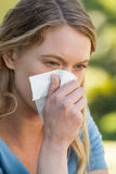 Woman blowing nose with tissue paper at park. Close-up of a young woman blowing nose with tissue paper at the park Stock Photos