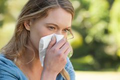 Woman blowing nose with tissue paper at park. Close-up of a young woman blowing nose with tissue paper at the park Stock Photography