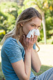 Woman blowing nose with tissue paper at park. Side view of a young woman blowing nose with tissue paper at the park Stock Images