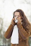 Woman blowing nose in winter outdoors. Young woman blowing nose in winter outdoors Royalty Free Stock Images