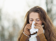 Woman blowing nose in winter outdoors Royalty Free Stock Image