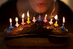 Woman is blowing out some colorful candles. On a marble cake Royalty Free Stock Image