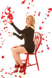 Woman blowing rose pedals sitting stock images