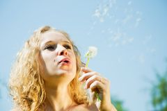 Woman blowing seeds of dandelion Stock Image