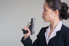 Woman blowing smoke off a hand gun Royalty Free Stock Photos