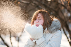 Woman blowing in the snow. Beautiful woman blowing in the snow Royalty Free Stock Photo