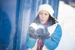 Woman blowing snow Stock Images