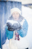 Woman blowing snow. Woman outdoors blowing snow on a cold winter day Stock Photo