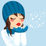 Woman Blowing Snow Christmas Magic. Beautiful brunette woman with warm blue winter hat and scarf gently blowing snow from her hands showing Christmas magic Stock Images