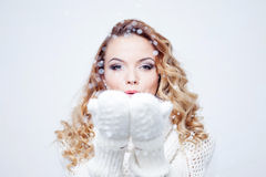 Woman Blowing Snow, girl in  warm knitted scarf Royalty Free Stock Photo