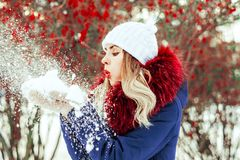 Woman blowing snow in hands. In slow motion Royalty Free Stock Images