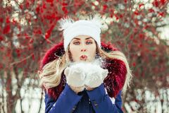 Woman blowing snow in hands. In slow motion Royalty Free Stock Image