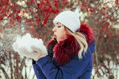 Woman blowing snow in hands. In slow motion Royalty Free Stock Photos