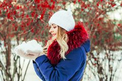 Woman blowing snow in hands. In slow motion Royalty Free Stock Photography