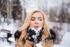 Woman blowing snow in hands in slow motion. royalty free stock images