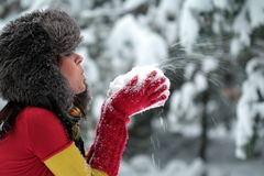 Woman blowing the snow in her hands. Woman in a fur cap blowing the snow kept in her hands Royalty Free Stock Image