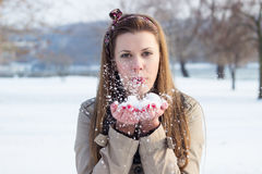 Woman blowing snow at you. Woman blowing snow from hands, winter Stock Photography