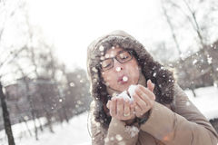 Woman blowing snowflakes from her hands Royalty Free Stock Images