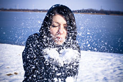 Woman blowing snowflakes in winter Stock Image
