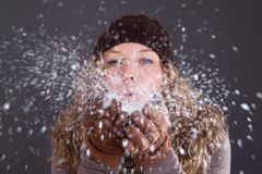 Woman blowing snowflakes Royalty Free Stock Image