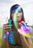 Woman blowing soap bubble. Wistful young woman blowing soap bubbles at summer Royalty Free Stock Photos