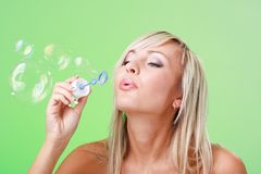 Woman blowing soap bubbles Stock Photos