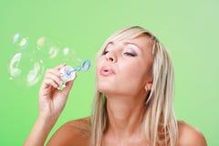 Woman blowing soap bubbles Stock Photos