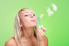 Woman blowing soap bubbles Stock Image