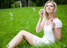 Woman is blowing soap bubbles Stock Photo