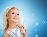 Woman blowing soap bubbles Royalty Free Stock Images