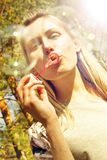 Woman blowing soap bubbles outdoors Stock Photos