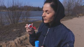 Woman blowing soap bubbles stock footage