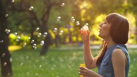 Woman blowing bubbles. Woman blowing soap bubbles at sunset stock footage