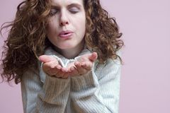 Woman blowing something. Woman blowing whatever you put in her hands Royalty Free Stock Photos