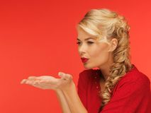 Woman blowing something on the palms of her hands Royalty Free Stock Photos