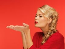 Woman blowing something on the palms of her hands Stock Photo