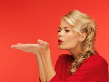 Woman blowing something on the palms of her hands Royalty Free Stock Image