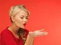 Woman blowing something on the palms of her hands Stock Images