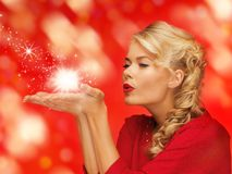 woman blowing something on the palms of her hands Royalty Free Stock Photo