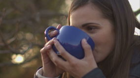 Woman blowing on the tea to cool down. Woman drinking a hot beverage from a large mug. Young woman standing under a tree and admire the autumn scenery stock footage